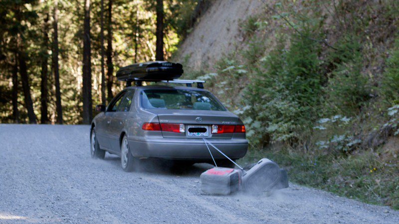A Toyota sedan is seen dragging coolers, tied to its trunk, over a gravel outdoor road.
