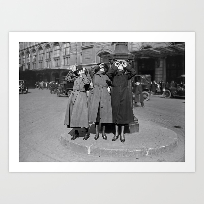 A photograph framed in white of three women in coats stand next to street lamp post gazing at the sky with some antiquated solar filters.