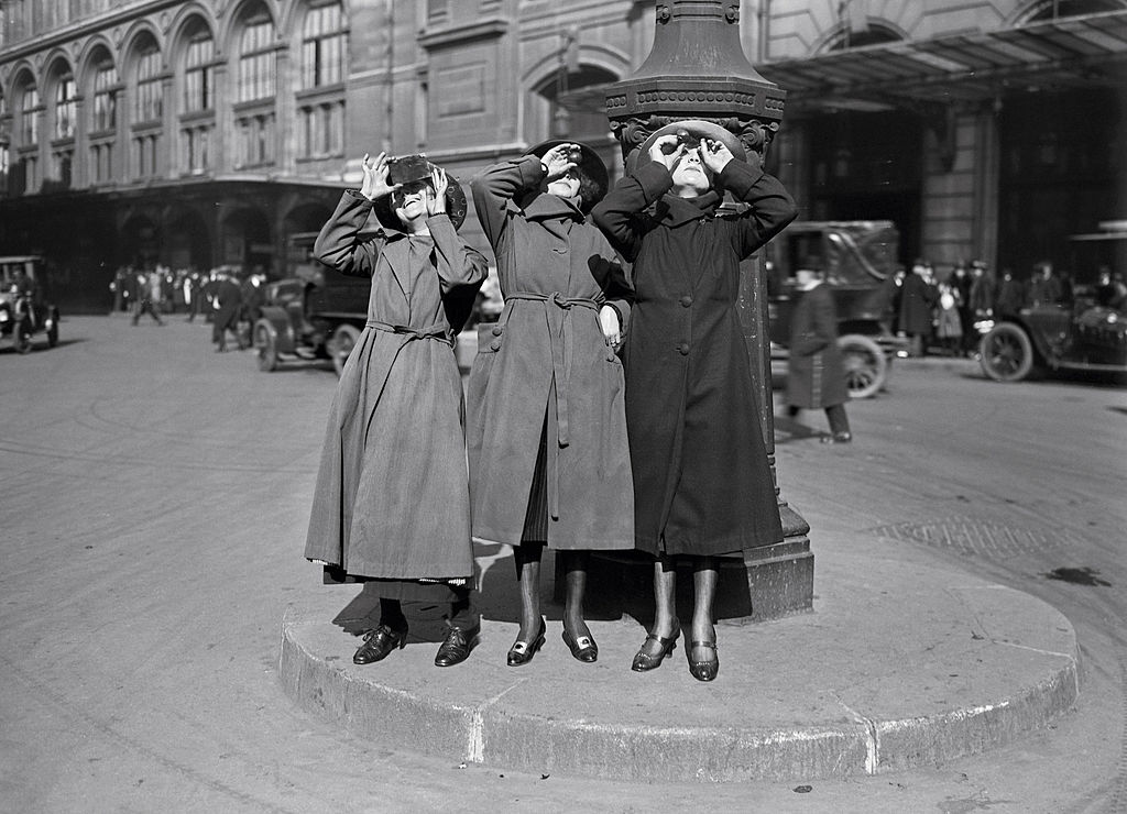 Three women in coats stand next to street lamp post gazing at the sky with some antiquated solar filters.