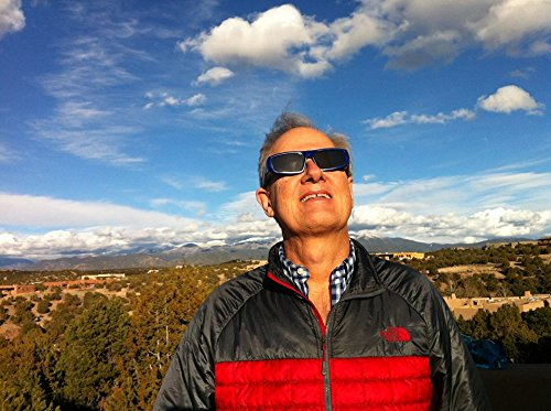 A 40 to 50 year old man in a gray and red The North Face puffy jacket is looking into the sky with premium solar eclipse sunglasses. Behind are mountiains and beautiful blue, somewhat cloudy, sky.