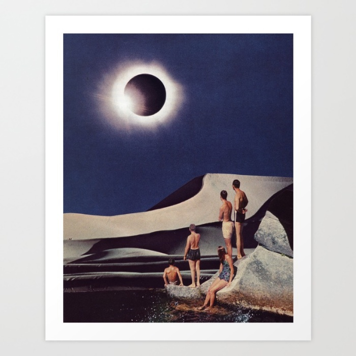 Five humans sit, in bathing suits, on a rock outcrop in a desert looking towards the sky where a total eclipse is seen.